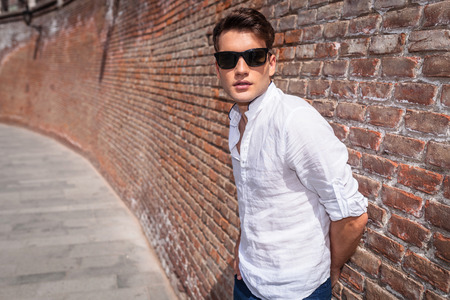 casual fashion: Side view of a casual fashion man leaning on a brick wall with his hand on the bak.