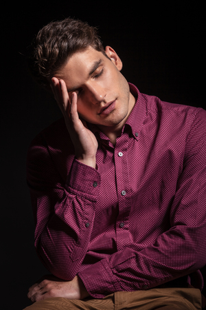 lean on hands: Young man leaning his head in his hand while holding his eyes closed.