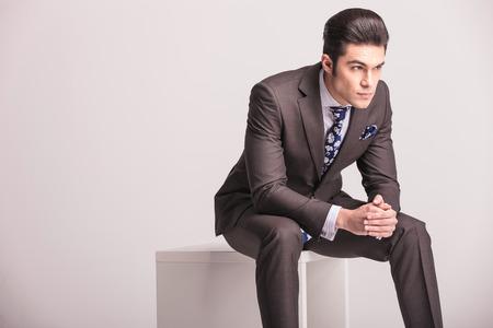 Zijaanzicht van een knappe jonge zakenman zit op een witte moderne stoel, met zijn handen samen.
