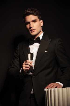 Attractive young business man holding his left hand on a column while holding a glass of champagne in his hand.
