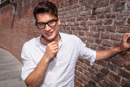 lean on hands: Smiling young fashion man looking to the camera while fixing his collar. Stock Photo