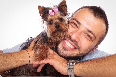 babyface: young man is holding his pet yorkshire terrier puppy dog and smiles to the camera Stock Photo