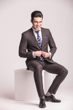 cerrando negocio: Feliz joven hombre de negocios de cerrar su chaqueta mientras est� sentado en una silla moderna blanco. Foto de archivo