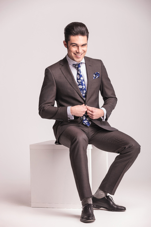 unbutton: Happy young business man closing his jacket while sitting on a white modern chair.