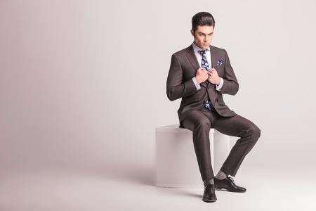 black hair: Foto de cuerpo entero de un joven elegante hombre de negocios sentado en una silla blanca mientras tira de su collar.