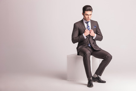 full suit: Full body picture of a young elegant business man sitting on a white chair while pulling his collar. Stock Photo