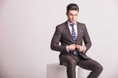 cerrando negocio: Joven hombre de negocios de cerrar su chaqueta mientras mira a la cámara. Él está sentado en una silla blanca.