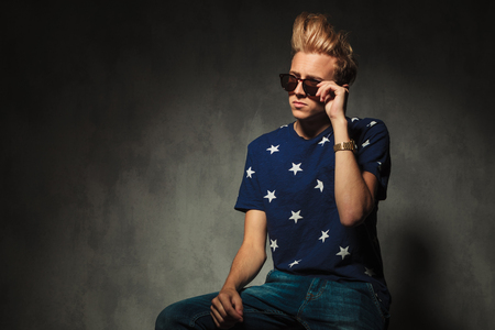 cool fashion holding his sunglasses while sitting on a chair in studio photo