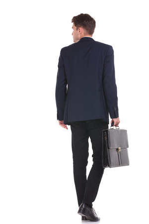 彼のブリーフケースを押しながら歩いている背の高いビジネスマンの背面します。 写真素材