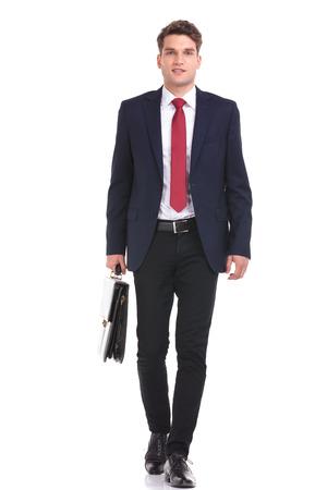 Smiling young business man walking on isolated background holding a briefcase.
