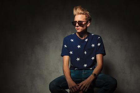 uomini belli: modello di moda fresca con occhiali da sole seduto su uno sgabello e guarda lontano dalla fotocamera ad un lato