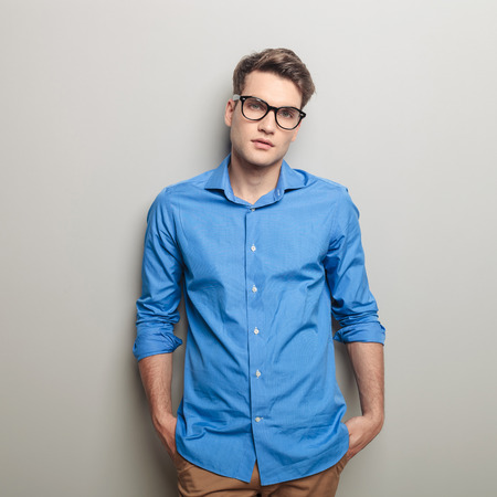 male models: Portrait of a handsome casual man looking at the camera while holding his hands in pockets. Stock Photo