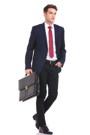 men standing: Side view of a handsome young business man walking with his hand in pocket while holding a briefcase.