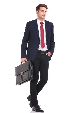 persona de pie: Vista lateral de un joven hombre de negocios que recorre con su mano en el bolsillo, mientras que la celebraci�n de un malet�n.