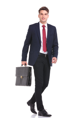 smiling businessman: Side view of a young business man holding a brief case while walking on isoaed background. Stock Photo