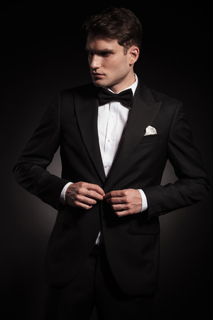 looking away from camera: Attractive young man closing his jacket while looking away from the camera. Stock Photo