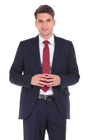 Handsome young business man smiling to the camera while holding his hands together.