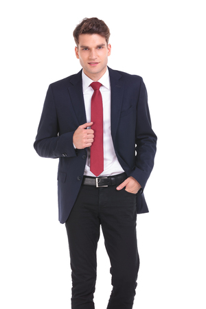 white suit: Front view of a young business man holding his hand in pocket.