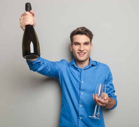 Attractive young man holding a bottle of champagne in his right hand and two glasses in his left hand.