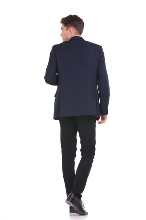 personas de espalda: Vista trasera de un hombre de negocios joven que camina mientras mira a su lado. Foto de archivo