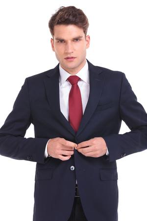 cerrando negocio: Joven hombre de negocios de cerrar su chaqueta mientras mira a la cámara.