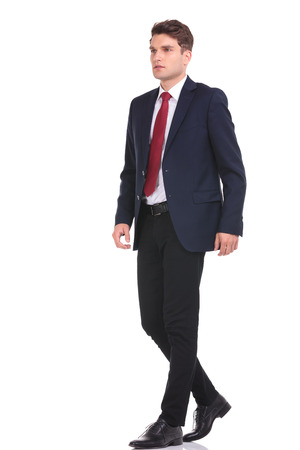 Full body of a young business man walking on isolated background. Stock Photo