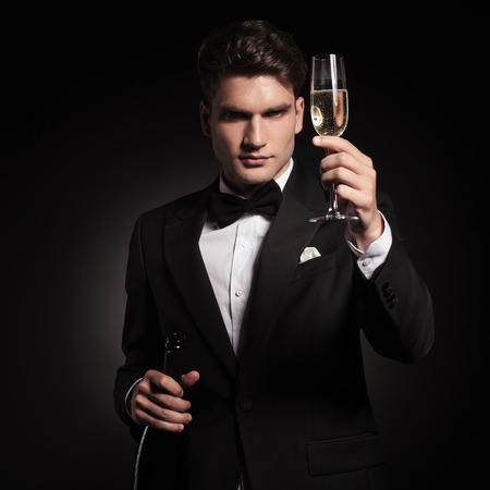 Young handsome elegant man holdinh up a glass of champagne. Stock Photo