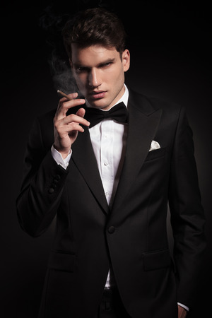 hand in pocket: Portrait of a elegant young man smoking a cigarette while holding his hand in pocket.