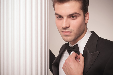 neck tie: Close up portrait of a handsome young business man looking away whie fixing his bowtie. Stock Photo