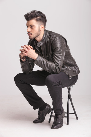 Side view picture of a fashion man holding his hands together while resting on a chair. 스톡 콘텐츠
