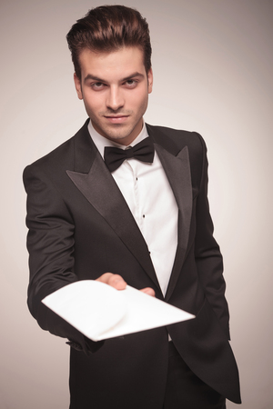man in tuxedo: Attractive young business man holding one hand in his pocket while offering you a invitation.