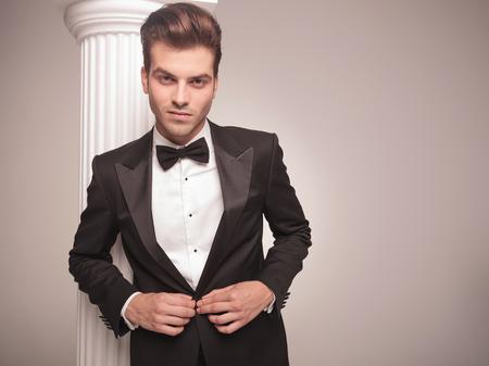 cerrando negocio: Retrato de un joven elegante hombre de negocios cerrando su chaqueta.