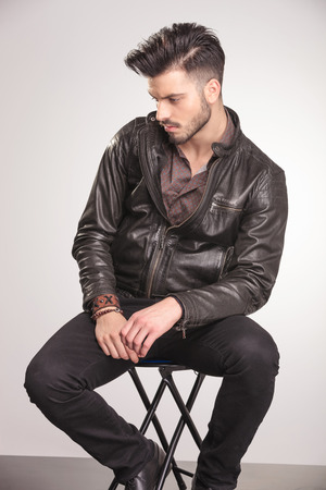leather coat: Side view of a handsome young fashion man sitting on a chair while looking down.