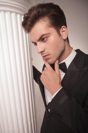 man looking down: Side view of a handsome business man looking down, thinking while holding his hand to his chin.
