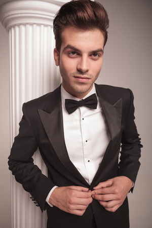 cerrando negocio: Cierre de imagen de un hombre de negocios joven y guapo cerrar su chaqueta sobre fondo gris studio.