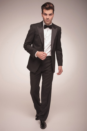 businessman walking: Full body picture of a handsome young business man walking on grey studio background, looking at the camera.