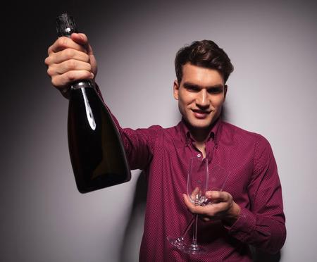 alzando la mano: Casual joven que presenta una botella de vino a la cámara mientras sostiene dos copas en la otra mano.