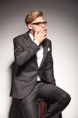 cigar smoke: Handsome business man sitting on a stool while smoking a cigarette, looking away from the camera.