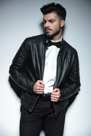 black professional: Attractive young business man looking to his side while pulling hisleather jacket.