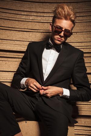 cerrando negocio: Rubio joven hombre de negocios de cerrar su chaqueta mientras mira hacia abajo.