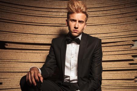 elegant business man: Giovane uomo elegante di affari che propone sullo sfondo di legno, guardando la telecamera. Archivio Fotografico