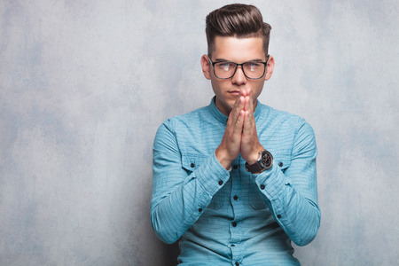 glasses model: young casual man praying