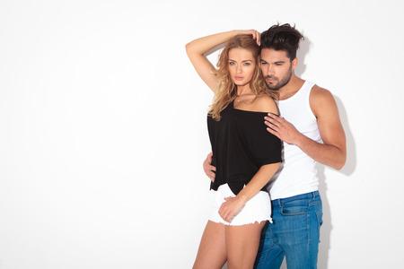 pantalones cortos: Pares de la manera que se inclina en una pared blanca, el hombre es abrazar a la mujer por detrás. Foto de archivo