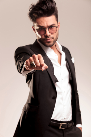 huge: Elegant business man holding one hand in his pocket while showing his fist at the camera. He is wearing a big gold ring on his hand.