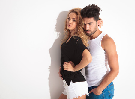 sexy couple embrace: Attractive fashion couple posing while embracing against a white wall.