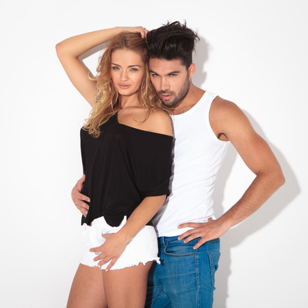 hot guy: Picture of a sexy young couple on white studio background. The man is embraing the woman while looking at the camera.
