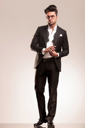 modelo: Hombre de negocios joven que fija su anillo de oro, mientras que mirando a la cámara, foto de cuerpo completo.