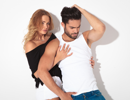 sexy couple embrace: Blonde woman looking at the camera while embracing her lover. He is fixing his hair while looking down. Stock Photo