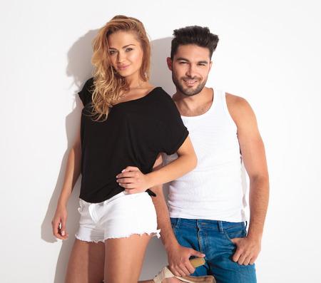 pantalones cortos: Pareja de moda sonriente posando juntos contra el fondo blanco. Foto de archivo