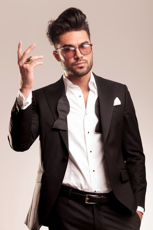 undone: Handsome young business man looking at the camera while showing his ring and holding one hand in his pocket. Stock Photo